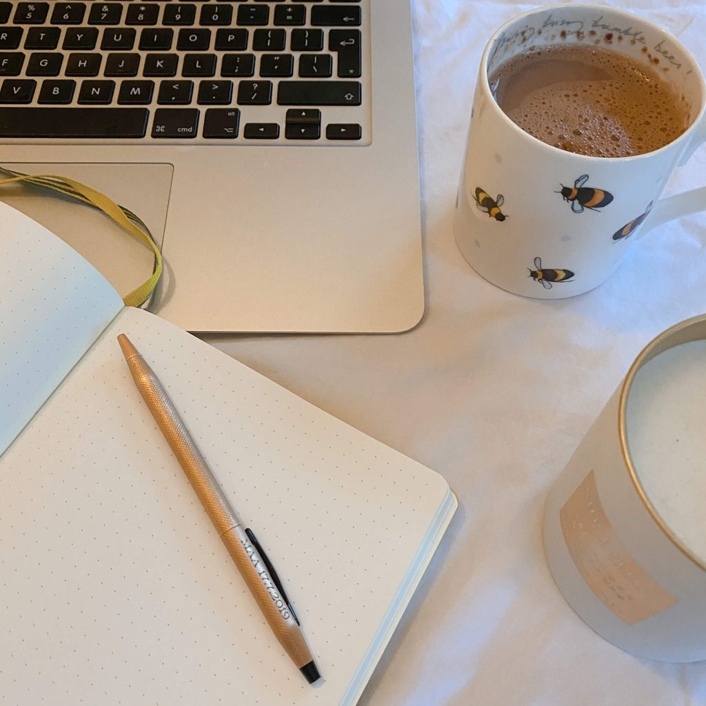 Feeling confident in your job application | photo shows a laptop, notepad, coffee and candle