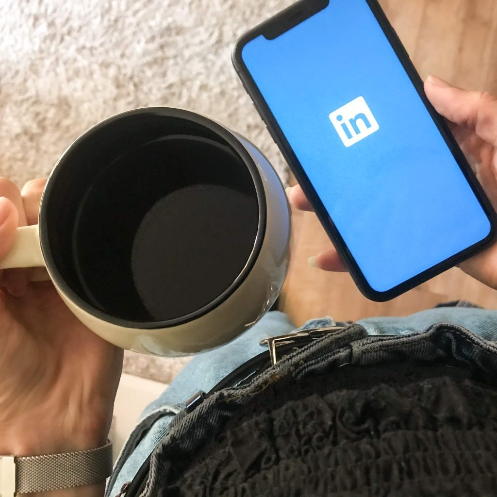 phone screen showing linkedin and holding a coffee