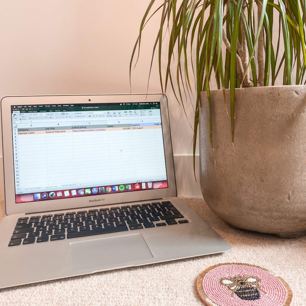 staying organised when job hunting | image shows a laptop with an excel spreadsheet, a plant and a bee coaster