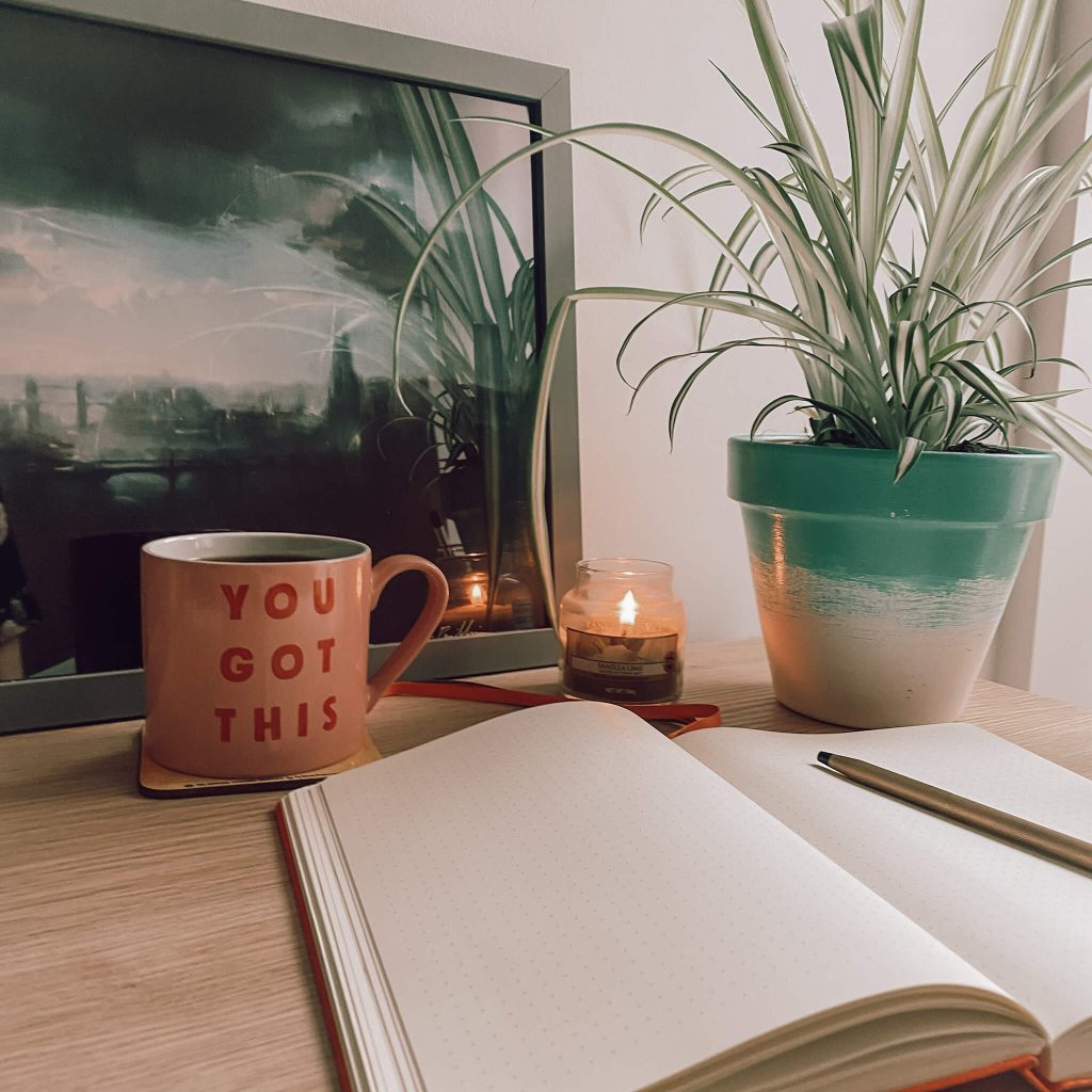 self care ideas | image shows an open notepad, a mug, and a plant on a desk with a lit candle